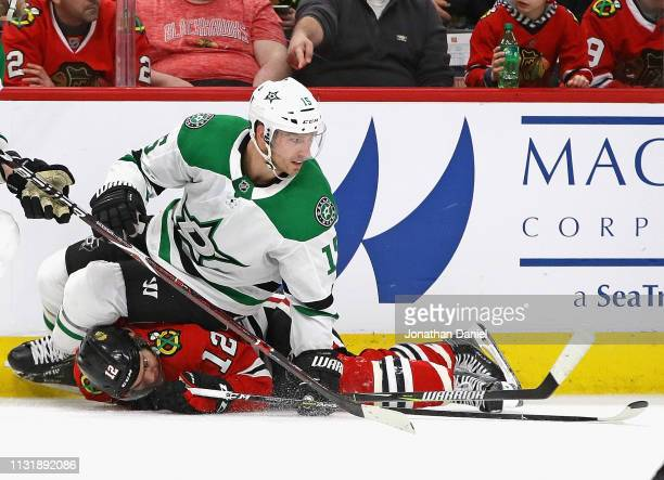 Blake Comeau of the Dallas Stars ands on top of Alex DeBrincat of the Chicago Blackhawks at the United Center on February 24 2019 in Chicago Illinois...