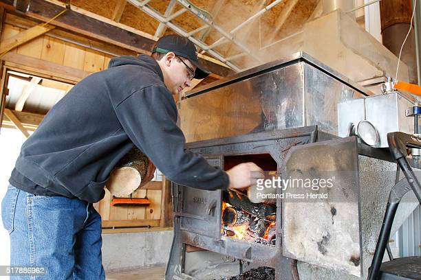 Blake Douston adds wood to the fire under his evaporator Sunday March 27 2016 during Maine Maple Sunday at Douston Maple and Honey in Alfred Maine