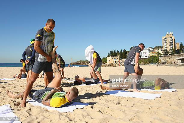 Blake Ferguson assists Josh Dugan during stretching at the Australia Kangaroos Test team recovery session at Coogee Beach on May 2 2016 in Sydney...