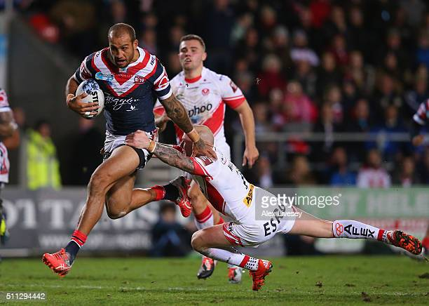 Blake Ferguson of Sydney Roosters holds off a challenge from Luke Walsh of St Helens on his way to scoring the third try during the World Club Series...