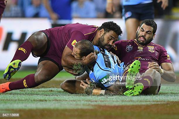 Blake Ferguson of the Blues is tackled by Sam Thaiday and Greg Inglis of the Maroons during game two of the State Of Origin series between the...