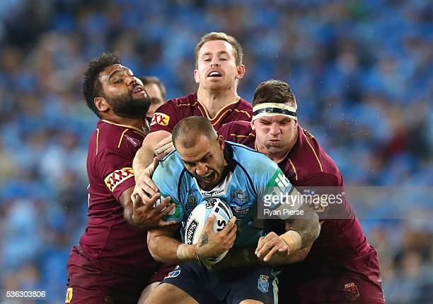 Blake Ferguson of the Blues is tackled by Sam Thaiday and Josh McGuire of the Maroons during game one of the State Of Origin series between the New...