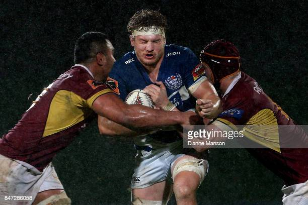 Blake Gibson of Auckland is tackled by Bill Fukofuka and Mike McKee of Southland during the round five Mitre 10 match between Southland and Auckland...