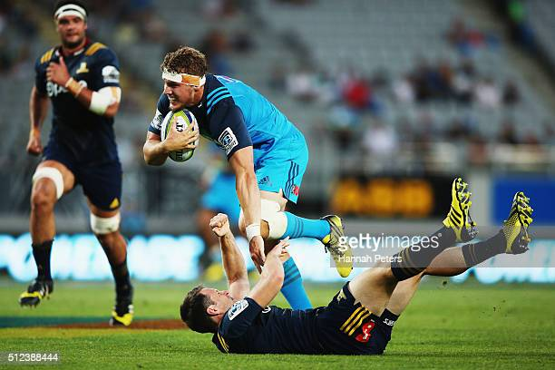 Blake Gibson of the Blues charges over Ben Smith of the Highlanders to score a try during the round one Super Rugby match between the Blues and the...