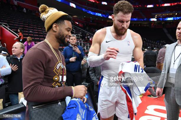 Blake Griffin of the Detroit Pistons signs a jersey for Darius Slay Jr of the Detroit Lions after the game on January 16 2019 at Little Caesars Arena...