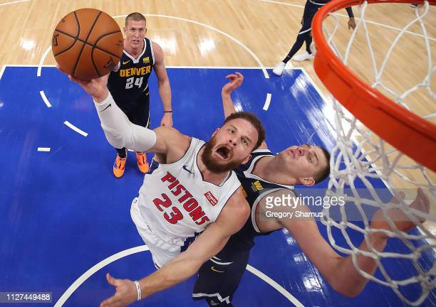 Blake Griffin of the Detroit Pistons tries to get a shot off around Nikola Jokic of the Denver Nuggets during the first half at Little Caesars Arena...