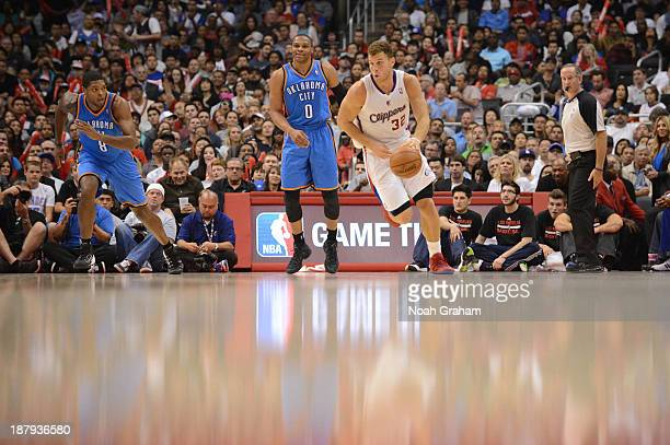 Blake Griffin of the Los Angeles Clippers drives upcourt against Ryan Gomes and Russell Westbrook of the Oklahoma City Thunder at Staples Center on...