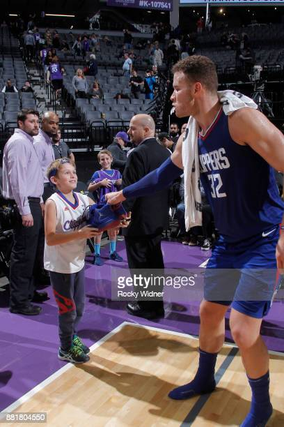 Blake Griffin of the Los Angeles Clippers gives his sneakers to a young fan after the game against the Sacramento Kings on November 25 2017 at Golden...