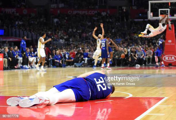 Blake Griffin of the Los Angeles Clippers lays on the court as he sustained a concussion after taking an elbow from JaVale McGee of the Golden State...