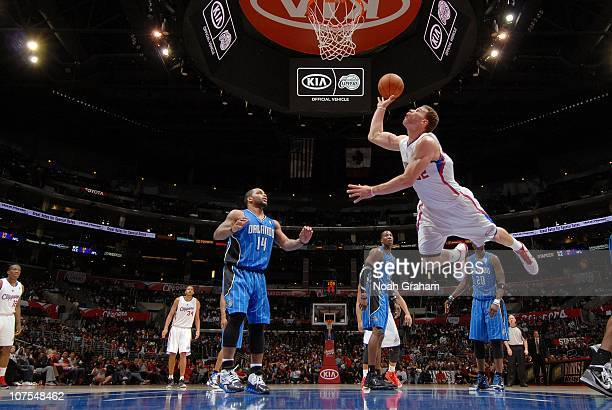 Blake Griffin of the Los Angeles Clippers puts up a shot as Jameer Nelson Dwight Howard and Mickael Pietrus of the Orlando Magic look on during the...