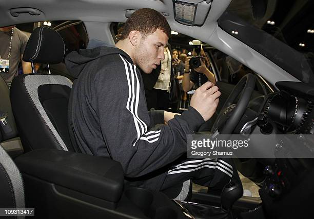 Blake Griffin of the Los Angeles Clippers signs the steering wheel of the Kia Optima he jumped over during Sprite Slam Dunk Contest at Jam Session...