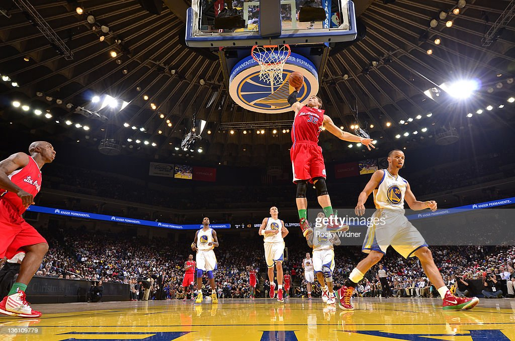 Blake Griffin #30 of the Los Angeles Clippers soars through the air for a dunk against Stephen Curry #30 of the Golden State Warriors on December 25, 2011 at Oracle Arena in Oakland, California.
