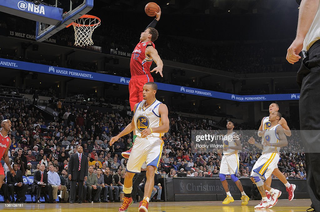 Blake Griffin #30 of the Los Angeles Clippers throws down a dunk against Stephen Curry #30 of the Golden State Warriors on December 25, 2011 at Oracle Arena in Oakland, California.