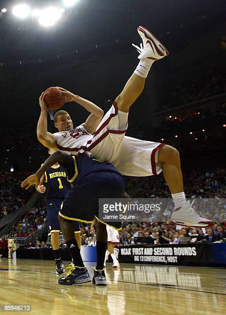 Blake Griffin of the Oklahoma Sooners falls on the back of Manny Harris of the Michigan Wolverines during the second round of the NCAA Division I...