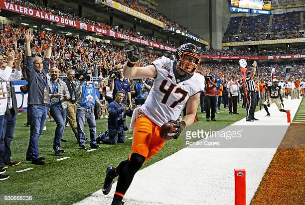 Blake Jarwin of the Oklahoma State Cowboys celebrates his touchdown reception against the Colorado Buffaloes of the Valero Alamo Bowl at the...