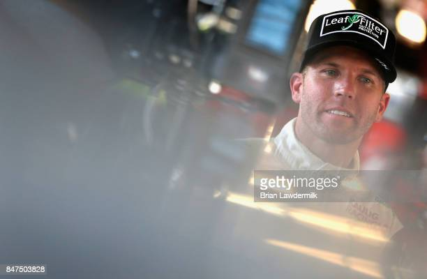 Blake Koch driver of the LeafFilter Gutter Protection Chevrolet stands in the garage area during practice for the NASCAR XFINITY Series TheHousecom...