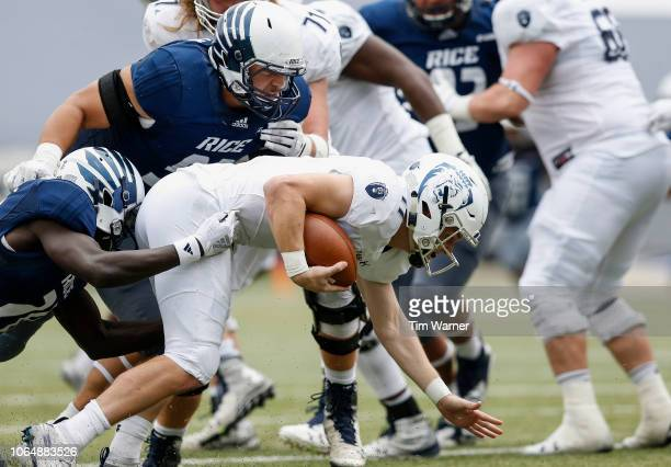 Blake LaRussa of the Old Dominion Monarchs is sacked by George Nyakwol of the Rice Owls and Trey Schuman in the second half at Rice Stadium on...