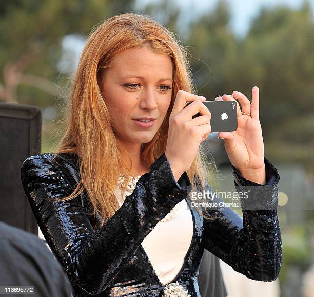 Blake Lively takes a photograph as the sun goes down during the Chanel Collection Croisiere Show 201112 at the Hotel du Cap on May 9 2011 in Cap...