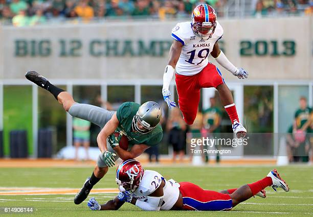 Blake Lynch of the Baylor Bears carries the ball against Isaiah Bean of the Kansas Jayhawks and Greg Allen of the Kansas Jayhawks in the fourth...