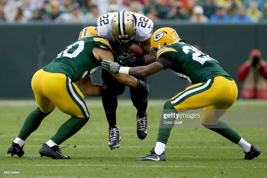 Blake Martinez #50 and Kevin King #20 of the Green Bay Packers tackle Mark Ingram #22 of the New Orleans Saints in the second quarter at Lambeau Field on October 22, 2017 in Green Bay, Wisconsin.