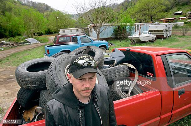 Blake Miller leans against a pickup truck loaded with used tires and parked outside his boyhood home in Jonancy Hollow, Ky. Located on the southern...