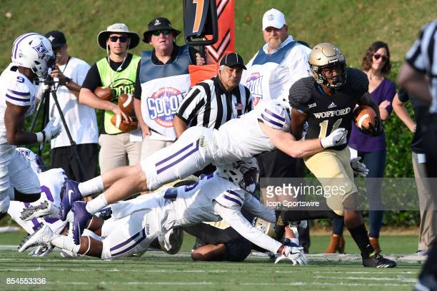 Blake Morgan halfback Wofford College Terriers attempts to break a tackle by Dillon Woodruff inside linebacker Furman University Paladins Saturday...