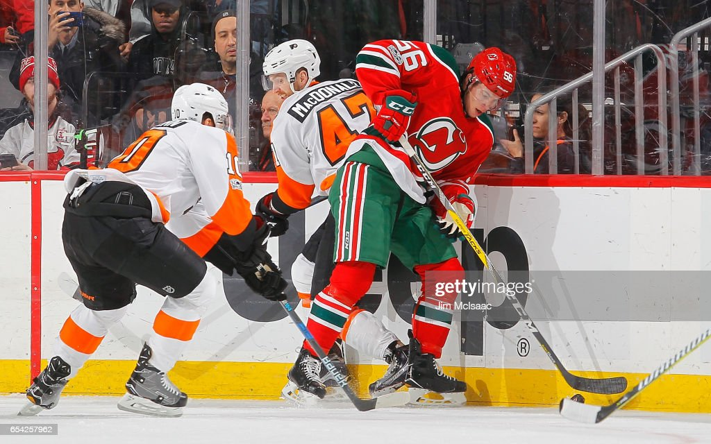Blake Pietila #56 of the New Jersey Devils plays the puck against Andrew MacDonald #47 and Brayden Schenn #10 of the Philadelphia Flyers on March 16, 2017 at Prudential Center in Newark, New Jersey.