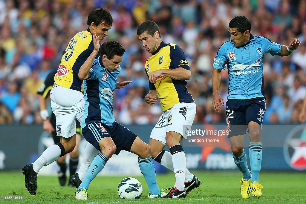 Blake Powell of Sydney competes with Nick Montgomery and Trent Sainsbury of the Mariners during the round 13 A-League match between Sydney FC and the Central Coast Mariners at Allianz Stadium on December 27, 2012 in Sydney, Australia.