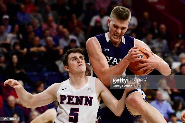 Blake Reynolds of the Yale Bulldogs grabs a rebound against Jackson Donahue of the Pennsylvania Quakers during the second half of a semifinal round...