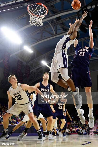 Blake Reynolds of the Yale Bulldogs Max Rothschild and AJ Brodeur of the Pennsylvania Quakers all look on as Trey Phills of the Yale Bulldogs and...