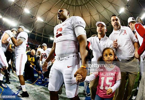 Blake Sims of the Alabama Crimson Tide celebrates their 42 to 13 win over the Missouri Tigers in the SEC Championship game with his daughter Kyla at...
