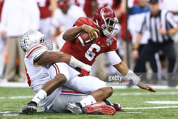 Blake Sims of the Alabama Crimson Tide gets sacked by the Ohio State Buckeyes during the All State Sugar Bowl at the MercedesBenz Superdome on...