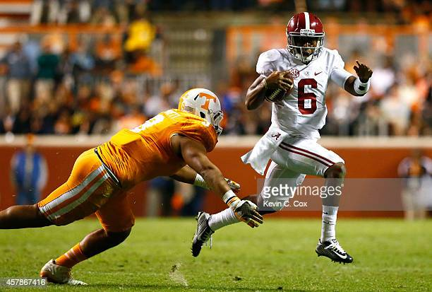 Blake Sims of the Alabama Crimson Tide rushes away from Derek Barnett of the Tennessee Volunteers at Neyland Stadium on October 25 2014 in Knoxville...