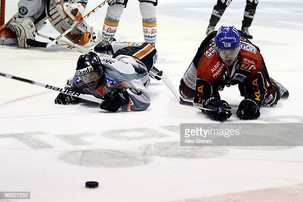 Blake Sloan of Wolfsburg and Colin Murphy of Augsburg look after the puck during the fourth DEL playoff semi final game between Augsburger Panther...