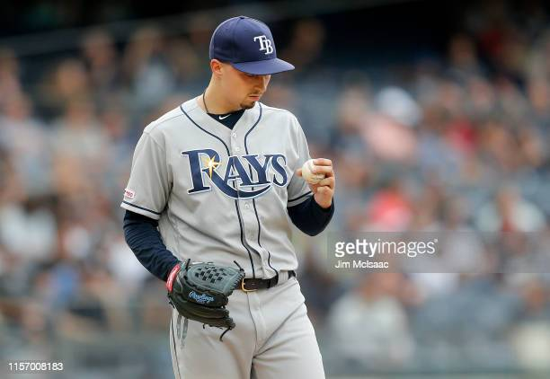 Blake Snell of the Tampa Bay Rays looks at the ball as he stands on the mound during the first inning against the New York Yankees at Yankee Stadium...