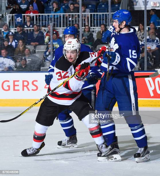 Blake Speers of the Albany Devils battles with Sergey Kalinin and Rinat Vailiev of the Toronto Marlies during game 3 action in the Division Semifinal...