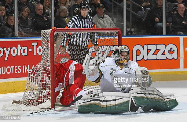 Blake Speers of the Sault Greyhounds ends up in the net behind Tyler Parsons of the London Knights during an OHL game at Budweiser Gardens on October...