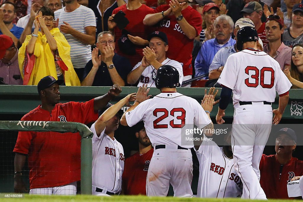 Blake Swihart #23 of the Boston Red Sox and Josh Rutledge #30 return to the dugout after scoring runs against the Chicago White Sox during the sixth inning at Fenway Park on July 30, 2015 in Boston, Massachusetts.