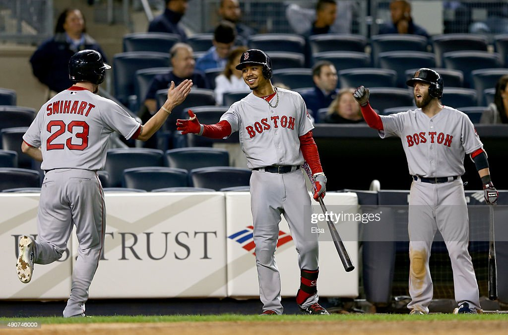 Blake Swihart #23 of the Boston Red Sox is congratulated by teammates Mookie Betts #50 and Dustin Pedroia #15 after Swihart scored in the 11th inning against the New York Yankees on September 30, 2015 at Yankee Stadium in the Bronx borough of New York City.