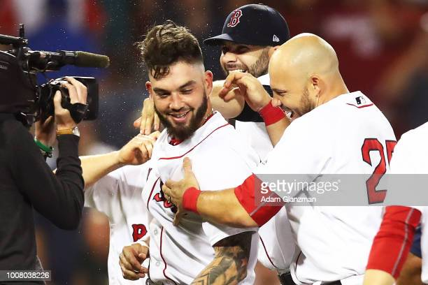 Blake Swihart of the Boston Red Sox is mobbed by his teammates after hitting the gamewinning walkoff groundrule double in the thirteenth inning of a...