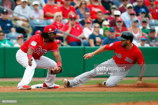 Blake Swihart of the Boston Red Sox slides in safe with a triple behind Maikel Franco of the Philadelphia Phillies in the first inning during a...