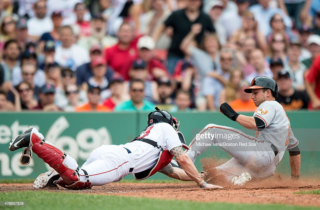 Blake Swihart #23 of the Boston Red Sox tags out David Lough #9 of the Baltimore Orioles to complete a double play during the ninth inning at Fenway Park in Boston, Massachusetts on June 25, 2015.