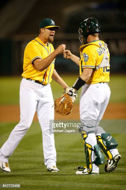 Blake Treinen and Dustin Garneau of the Oakland Athletics celebrate on the field following the game against the Kansas City Royals at the Oakland...