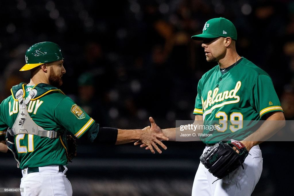 Blake Treinen #39 of the Oakland Athletics celebrates with Jonathan Lucroy #21 after the game against the Baltimore Orioles at the Oakland Coliseum on May 4, 2018 in Oakland, California. The Oakland Athletics defeated the Baltimore Orioles 6-4.