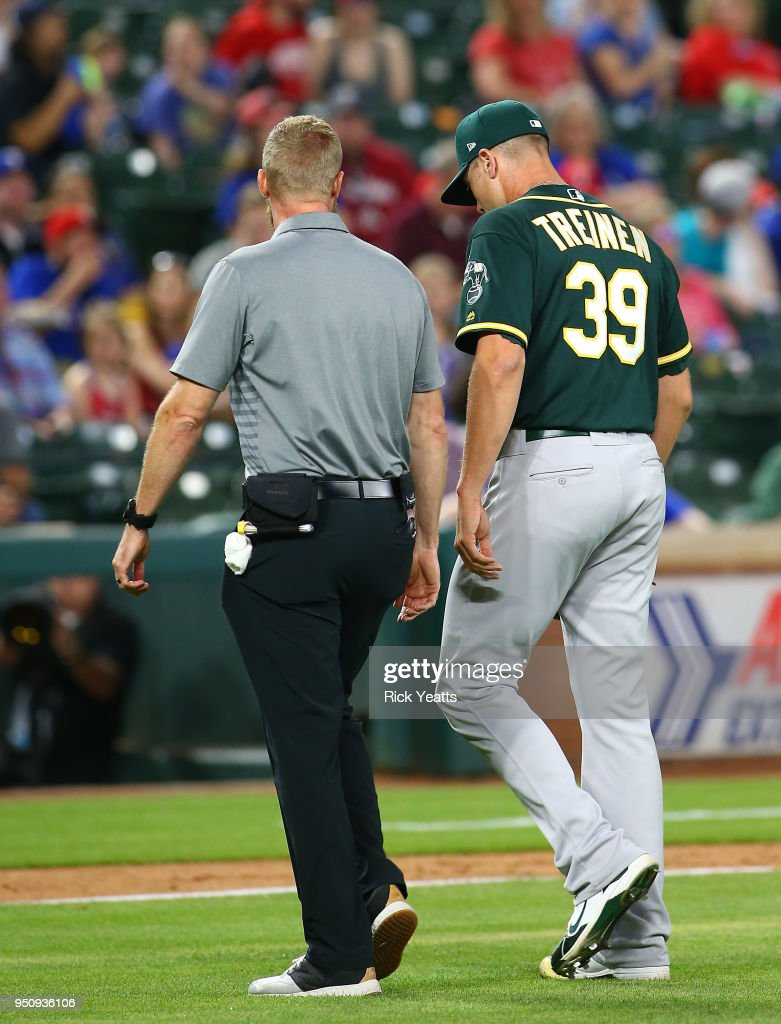 Blake Treinen #39 of the Oakland Athletics walks off the field with the trainer after getting hit by a line drive ball in the eighth inning against the Texas Rangers at Globe Life Park in Arlington on April 24, 2018 in Arlington, Texas.