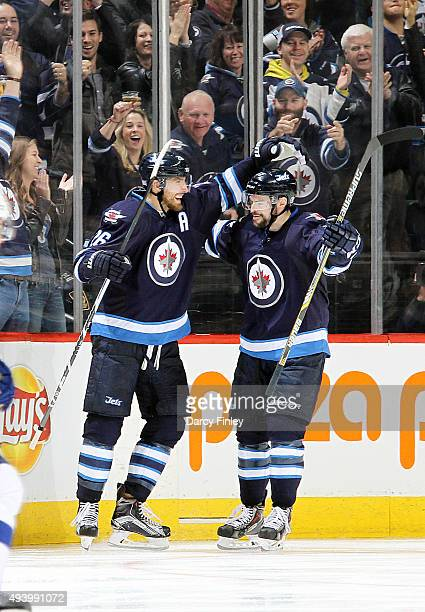 Blake Wheeler and Drew Stafford of the Winnipeg Jets celebrate a third period goal against the Tampa Bay Lightning at the MTS Centre on October 23...