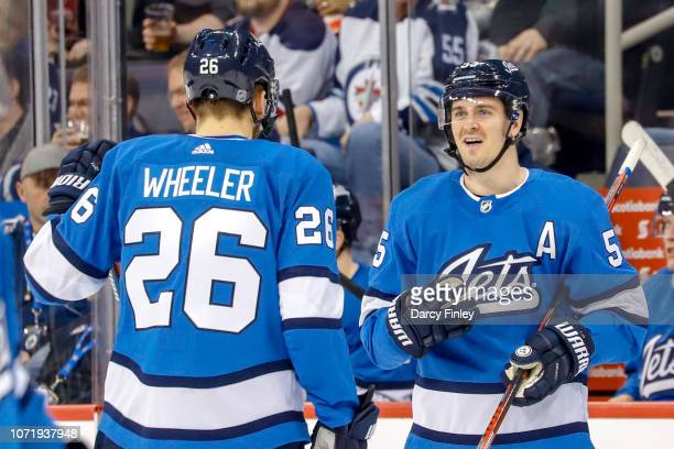 Blake Wheeler and Mark Scheifele of the Winnipeg Jets discuss strategy during a third period stoppage in play against the Chicago Blackhawks at the...