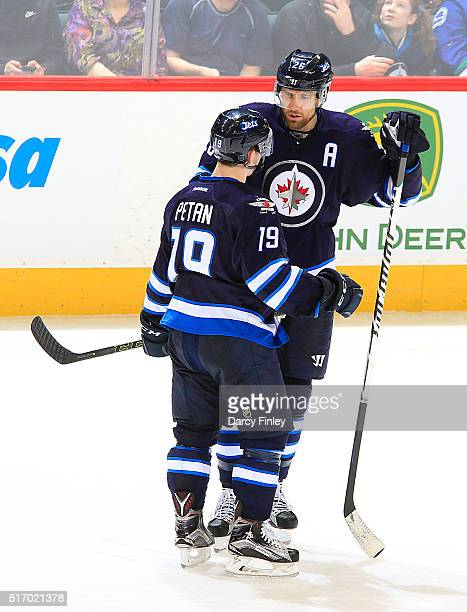Blake Wheeler and Nic Petan of the Winnipeg Jets discuss strategy during a second period stoppage in play against the Vancouver Canucks at the MTS...