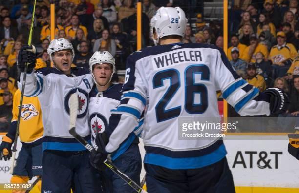 Blake Wheeler and Tyler Myers of the Winnipeg Jets congratulate teammate Mark Scheifele on scoring a goal against the Nashville Predators during the...