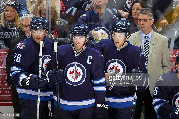 Blake Wheeler Andrew Ladd Eric Tangradi and Head Coach Claude Noel of the Winnipeg Jets look on from the bench during the first period against the...
